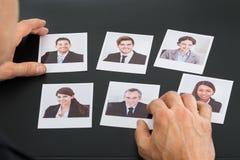 拿着候选人的照片商人 免版税库存图片