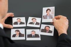 拿着候选人的照片商人 免版税图库摄影