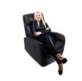 Усмехаясь девушка сидя в кресле Стоковые Фотографии RF