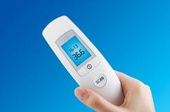拿着数字式不接触的温度计的手 免版税库存照片