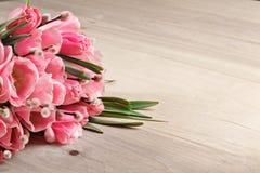桃红色新鲜的郁金香花束在木背景的 免版税库存照片