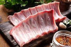 Ακατέργαστο κρέας πλευρών χοιρινού κρέατος στον ξύλινο τέμνοντα πίνακα Στοκ εικόνα με δικαίωμα ελεύθερης χρήσης