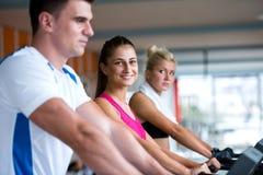 行使在踏车的朋友在明亮的现代健身房 免版税库存照片