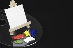 微型画架和空白的白色帆布 库存照片