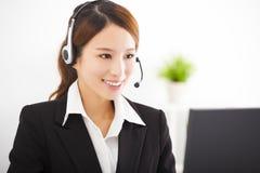 有耳机的年轻亚裔女实业家在办公室 免版税图库摄影