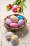 新鲜的郁金香和五颜六色的复活节彩蛋在巢 免版税库存图片