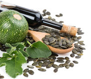 玻璃瓶南瓜籽油,南瓜和被剥皮的南瓜看见 免版税图库摄影