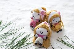 三天使放松在雪的睡眠,玩偶手工制造概念 免版税库存照片