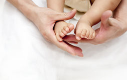 Τα χέρια του γονέα κρατούν στενό επάνω ποδιών μωρών ενός έτους βρεφών πέρα από το λευκό Στοκ Φωτογραφίες