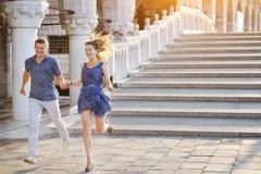 微笑和跑在威尼斯,意大利的愉快的夫妇 免版税库存图片