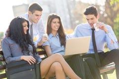 Молодые бизнесмены на скамейке в парке Стоковые Фотографии RF