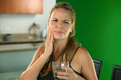 有牙痛的少妇喝冷水的 免版税库存照片