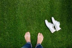 基于与说谎的运动鞋的绿草的脚 库存照片