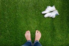 基于与说谎的运动鞋的草的脚 图库摄影