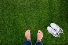 基于与运动鞋的绿草的脚 免版税图库摄影