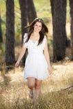 白色礼服的愉快的少妇走本质上的 图库摄影