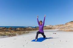 在海滩的实践的瑜伽 免版税库存图片