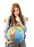 美丽的学生女孩在她的手上的拿着世界地球选择在旅行旅游业概念的假日目的地 图库摄影