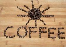 文字和太阳形象由新鲜的咖啡豆制成在老木背景 免版税库存图片