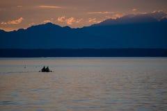 荡桨在有山的一条小船的两个人剪影在距离 免版税库存照片