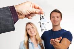 年轻夫妇的房地产经纪商移交的议院钥匙 免版税图库摄影