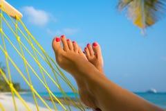 在吊床的妇女脚在海滩 免版税库存图片