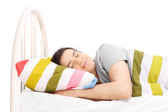 演播室睡觉在床上的射击了一个无忧无虑的人 免版税库存照片