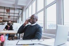 年轻人谈话在他的手机在办公室 库存照片