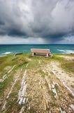 在海附近的长凳有风雨如磐的云彩的 免版税库存图片