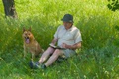 读一本有趣的书的成熟人对幼小狗 免版税图库摄影