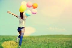 有色的气球的年轻亚裔妇女 免版税库存图片