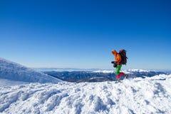 远足在雪靴的山的冬天有背包和帐篷的 免版税库存图片