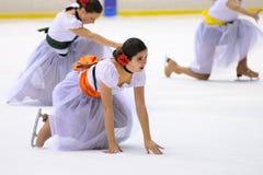 从学校的年轻队滑冰在冰执行,假装当佛拉明柯舞曲舞蹈家 免版税图库摄影