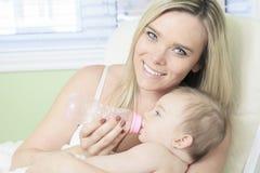 在家喂养他们新的女婴的年轻母亲 库存图片