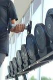 Το ισχυρό χέρι γυναικών παίρνει έναν βαρύ αλτήρα στη γυμναστική Στοκ εικόνες με δικαίωμα ελεύθερης χρήσης