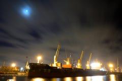 与起重机的装货货船在口岸被停泊在晚上 免版税库存照片