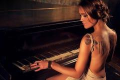 演奏妇女年轻人的钢琴 免版税库存照片