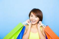拿着购物袋的少妇在蓝色背景前 免版税库存图片