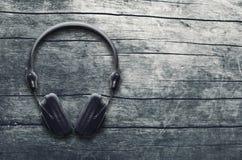 音乐难看的东西背景,在一张木桌上的黑耳机 库存图片