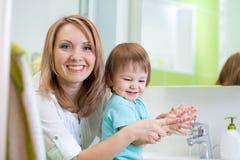 有肥皂的愉快的母亲和儿童洗涤的手 免版税库存照片