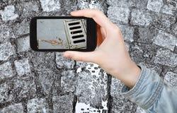 Τουρίστας που παίρνει τη φωτογραφία του υγρού δρόμου κυβόλινθων Στοκ Εικόνα