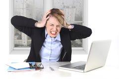 年轻女实业家恼怒在重音在研究计算机的办公室 免版税库存照片