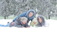 家庭在冬天多雪的公园 免版税库存照片