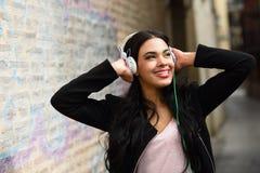 在都市背景中听到与耳机的音乐的妇女 免版税库存图片