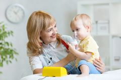 医生藏品孩子呼吸的吸入器屏蔽 免版税图库摄影