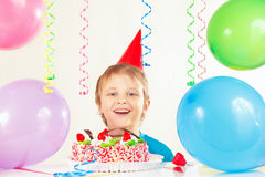 欢乐帽子的年轻男孩有生日蛋糕和气球的 免版税库存图片