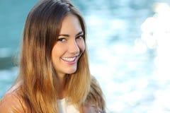 有完善的微笑和白色牙的愉快的女孩在海滩 免版税库存照片