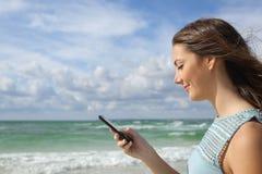 使用在海滩的女孩的档案一个巧妙的电话 免版税库存图片