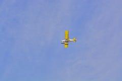 飞机飞行黄色反对与云彩的蓝天 免版税库存图片