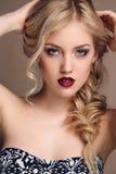 有白肤金发的卷发的肉欲的妇女有明亮的构成的 免版税库存照片